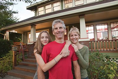 Father, mother and daughter standing in front of classic craftsman home, portrait
